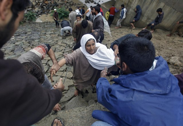 Kashmiri men pull a woman from the side embankment of a bridge during rain in Srinagar September 6, 2014. (Photo by Danish Ismail/Reuters)