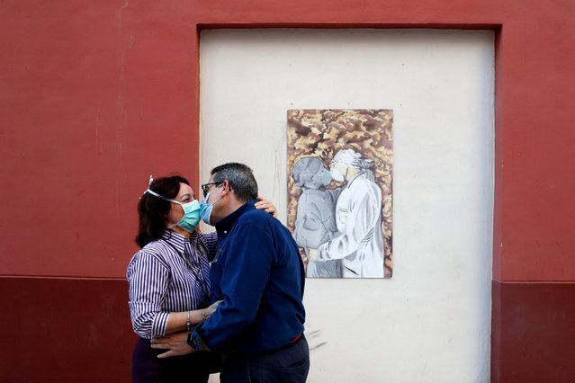 Nurse couple, Maria Rosa Iglesias and Alfonso Garcia, both 58, wearing protective masks, kiss each other as they pose for a photo next to a wall painting in a street, in support of healthcare workers, as most Spanish provinces are allowed to ease restrictions during phase one amid the coronavirus disease (COVID-19) outbreak, in Malaga, Spain, May 18, 2020. (Photo by Jon Nazca/Reuters)