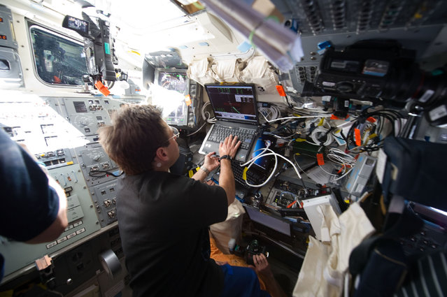 NASA astronaut Greg Chamitoff uses a laptop computer on the aft flight deck of space shuttle Endeavour during rendezvous and docking operations with the International Space Station in this photograph provided by NASA and taken May 18, 2011. (Photo by Reuters/NASA)
