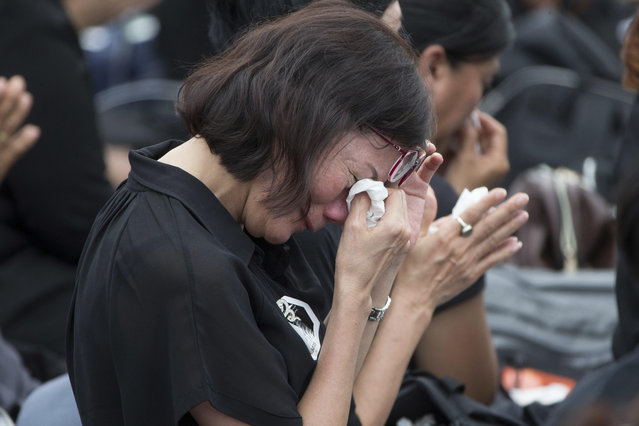 A mourner cries during the funeral procession and royal cremation ceremony of late Thai King Bhumibol Adulyadej, in Bangkok, Thailand, Thursday, October 26, 2017. Tearful Thais clad in black mourned on Bangkok's streets or at viewing areas around the nation Thursday as elaborate funeral ceremonies steeped in centuries of royal tradition were held for King Bhumibol Adulyadej following a year of mourning. (Photo by Wason Wanichakorn/AP Photo)