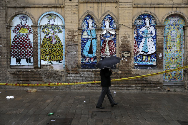 A man shelters from the rain with an umbrella a he walks past an old building decorated with replica of Iranian old paintings in a mostly empty street in a commercial district in downtown Tehran, Iran, Sunday, March 22, 2020. On Sunday, Iran imposed a two-week closure on major shopping malls and centers across the country to prevent spreading the new coronavirus. Pharmacies, supermarkets, groceries and bakeries will remain open. (Photo by Vahid Salemi/AP Photo)