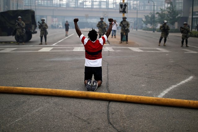 A man reacts as he confronts National Guard members guarding the area in the aftermath of a protest after a white police officer was caught on a bystander's video pressing his knee into the neck of African-American man George Floyd, who later died at a hospital, in Minneapolis, Minnesota, May 29, 2020. (Photo by Carlos Barria/Reuters)