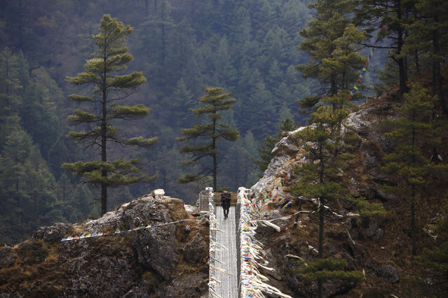 A porter crosses a bridge while on his way back from Namche, approximately 11155 feet above sea level in Solukhumbu District April 26, 2014. (Photo by Navesh Chitrakar/Reuters)