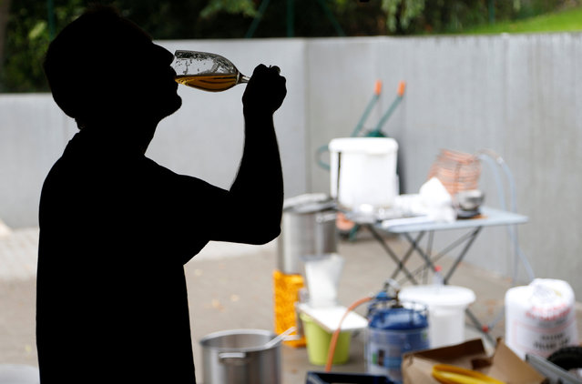 Simon Royer, medical student and member of the Belgian Homebrewers association, tastes his own beer outside his parents garage in Wepion, Belgium, August 11, 2016. (Photo by Francois Lenoir/Reuters)