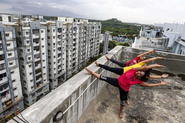 Yoga instructors from Anahata Yoga Zone perform yoga postures on a building's terrace in Hyderabad on June 18, 2020, ahead of the International Yoga Day annually celebrated on June 21. (Photo by Noah Seelam/AFP Photo)