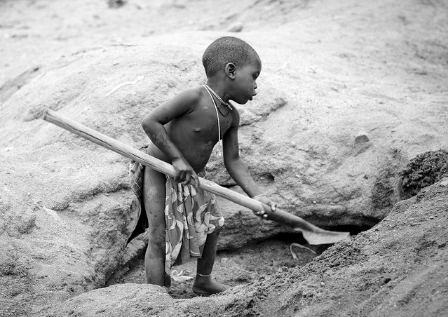 """Mucubal kid digging for water – Angola. Mucubal near Virie grow corn, as they have access to good wells. But the daily work is to dig the well to rech the water which can be 2 or 3 meters deep.This little kid imitates the adults and help them"". (Eric Lafforgue)"