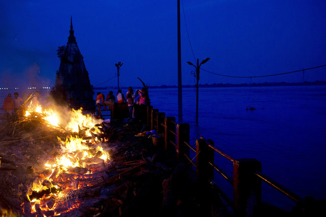 In this Thursday, August 25, 2016 photo, Hindu funerals are performed atop of a Hindu temple at the flooded Manikarnika Ghat in Varanasi, India. (Photo by Tsering Topgyal/AP Photo)