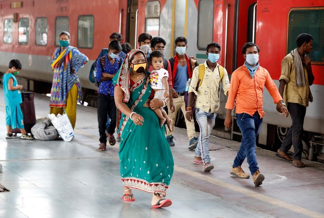 Migrant workers and their families, who had left during a lockdown, walk at a platform after they returned from their home state of Uttar Pradesh, after authorities eased lockdown restrictions that were imposed to slow the spread of the coronavirus disease (COVID-19), in Ahmedabad, India on July 1, 2020. (Photo by Amit Dave/Reuters)
