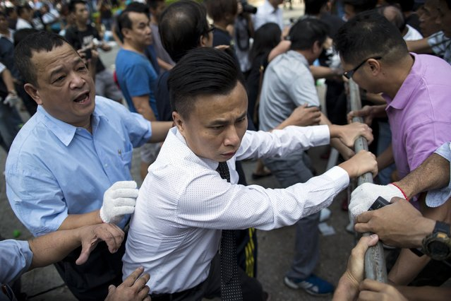 A office worker (2nd L) rushes to join pro-democracy protesters as they attempt to reinforce their barricades, as anti-Occupy Central protesters try to remove the road blocks, in the Central financial district in Hong Kong October 13, 2014. (Photo by Tyrone Siu/Reuters)