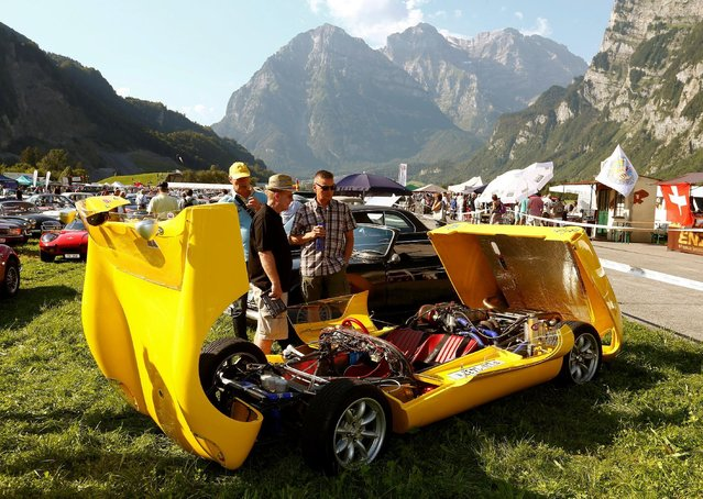 Three men stand behind a Lotus Type 23 sports car with opened bonnets during the British Car Meeting 2016 in the village of Mollis, Switzerland August 28, 2016. (Photo by Arnd Wiegmann/Reuters)