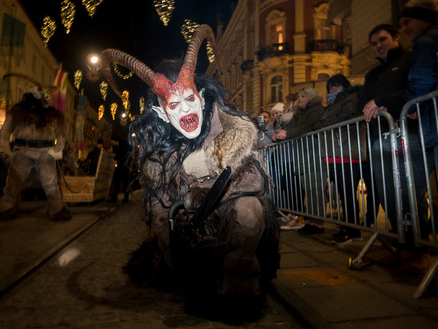 "A devil character seen running in the centre of Graz, Austria on December 3, 2017. Around December 6th, St. Nicolas Day, people dress up as devils run through streets of towns and villages in Austria. They seem like if they jumped out from a horror movie. Or from the hell. They are dressed in animal skins, have horns, strange instruments to scary people. Their faces are turned into nasty grins. They are covered with blood and scars and their long teeth dangle out of their mouths. Special tradition of a devil characters named ""krampus"" and ""percht"" who are coming with the St. Nicolas to punish bad people was born in remote valleys of Alp mountains hundreds years ago. Long winter nights were full of monsters. But at the end, krampus and percht were not just negative characters. They came to punish everything bad and prepare people for a new start. All the negative things in the village should be forgotten after krampus night. Until now, people dress animal skins and wooden masks to run and scare the audience. They are accompanied by pyrotechnic and light effects and hard music. They keep the tradition clear: no plastic. No Hollywood. Just wooden masks are allowed. Masks cost between 600 to 1200 euro each. Plus horns, animal skin for clothes and special shoes. Some groups come with strange vehicles. They prepare new performance each year. (Photo by Jana Cavojska/SOPA Images/LightRocket via Getty Images)"