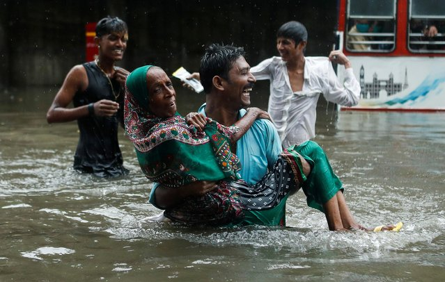 A man carries an elderly woman as they cross a waterlogged street during heavy rainfall in Mumbai, India, July 15, 2020. (Photo by Francis Mascarenhas/Reuters)