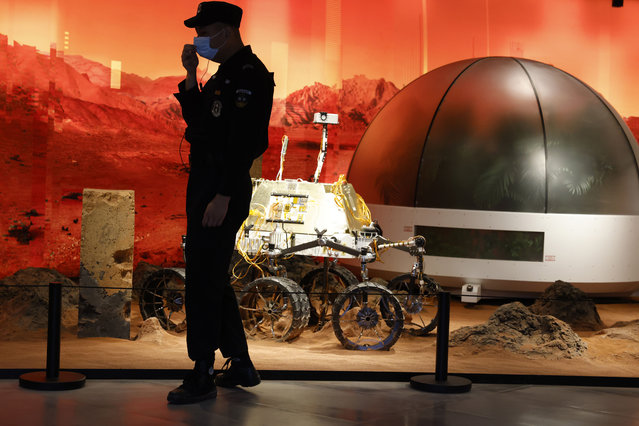 A security guard adjusts his mask near an exhibition of rovers and bio-domes on Mars in Beijing Thursday, July 23, 2020. China launched its most ambitious Mars mission yet on Thursday in a bold attempt to join the United States in successfully landing a spacecraft on the red planet. The Tianwen-1 was launched on a Long March-5 carrier rocket from a launch site on Hainan Island. (Photo by Ng Han Guan/AP Photo)