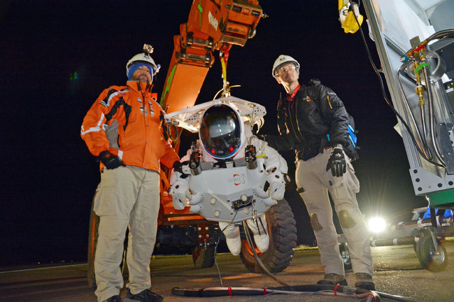 In this photo provided by Paragon Space Development Corporation, Google executive Alan Eustace, in the spacesuit, is shown with crew members Blikkies Blignaut, left, and Alex Garbino in preparation his leap from the edge of space that broke the sound barrier and set several skydiving records over the southern New Mexico desert outside Roswell Friday, October 24, 2014. (Photo by AP Photo/Paragon Space Development Corporation)