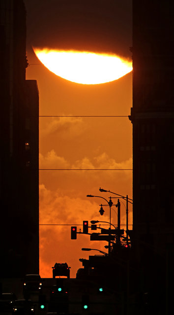 The sun dips behind a cloud as it rises between tall buildings in downtown Kansas City, Mo. Wednesday, September 23, 2015. (Photo by Charlie Riedel/AP Photo)