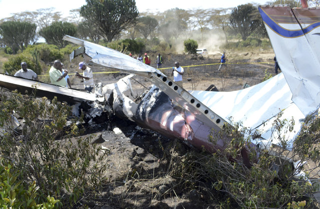 Police and members of the public observe the wreckage of a light plane that crashed near Sanctuary Farm in Naivasha, Kenya, Thursday, September 8, 2016. A Kenyan police official says one person died and five others survived when the plane crashed near the airstrip in Kenya's Rift Valley. (Photo by AP Photo)