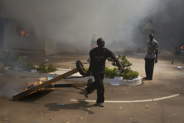 An anti-government protester carries a burning object outside the parliament building in Ouagadougou, capital of Burkina Faso, October 30, 2014. (Photo by Joe Penney/Reuters)