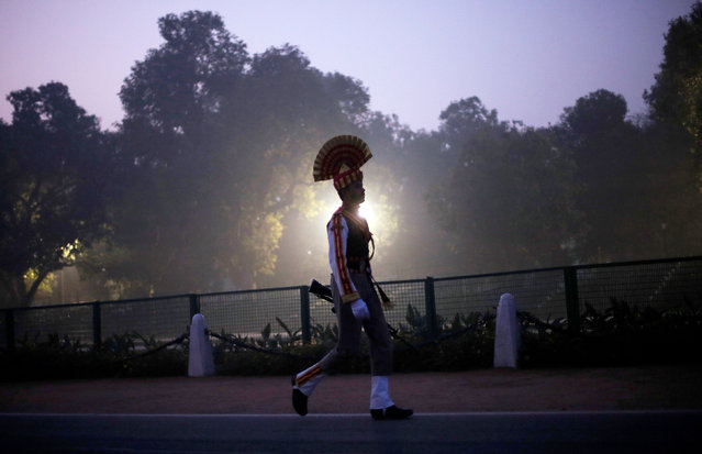 A soldier carries his gun as he walks to join others during the rehearsal for the Republic Day parade on a winter morning in New Delhi, January 8, 2018. (Photo by Adnan Abidi/Reuters)