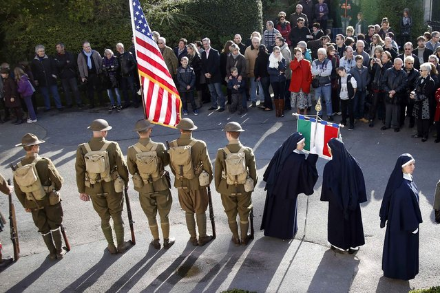 """History enthusiasts of French association """"Rock of the Marne"""" dressed as U.S. soldiers (L) and Italian nurses (R) attend an Armistice Day ceremony to commemorate the end of World War One at Epernay, eastern France, November 11, 2014. (Photo by Charles Platiau/Reuters)"""