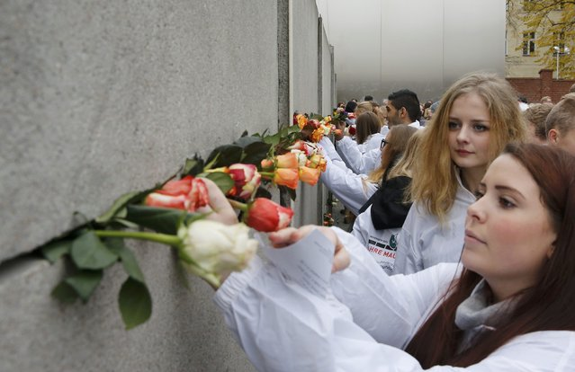 People wearing Travel For Peace (Aktive Fredsreiser) jackets place roses at the Berlin Wall memorial in Bernauer Strasse, during a ceremony marking the 25th anniversary of the fall of the Berlin Wall, in Berlin November 9, 2014. (Photo by Fabrizio Bensch/Reuters)