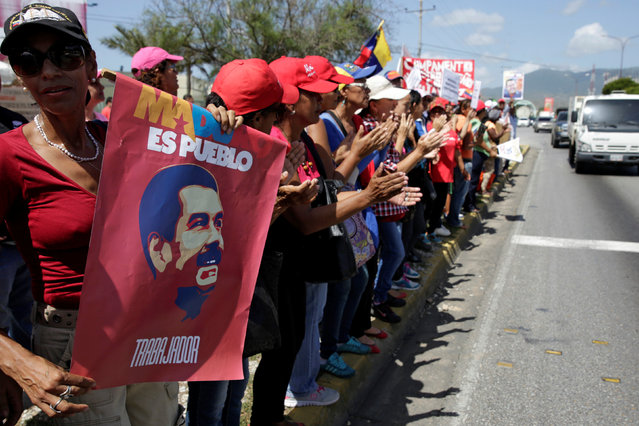 Supporters of Venezuela's President Nicolas Maduro gather in a street near the Venetur Hotel Convention Center where the 17th Non-Aligned Summit takes place in Porlamar, Venezuela September 16, 2016. (Photo by Marco Bello/Reuters)