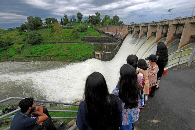 People watch the Rawal Dam after the spillway opened due to heavy monsoon rains, in Islamabad on August 31, 2020. More than 100 Pakistanis died in August because of the monsoon, which has also destroyed more than 1,000 homes. (Photo by Aamir Qureshi/AFP Photo)