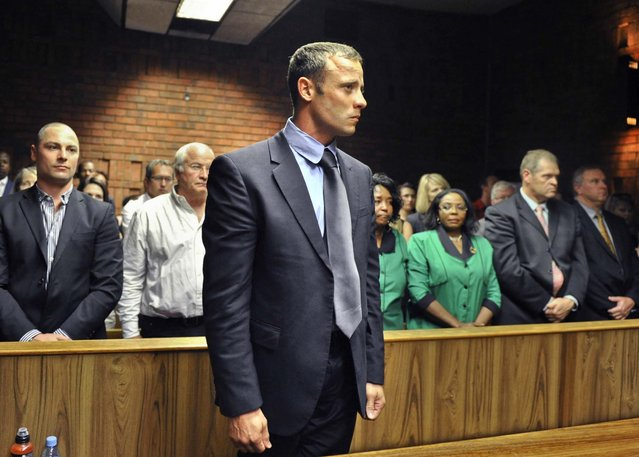 Olympic runner Oscar Pistorius stands following his bail hearing in Pretoria, South Africa, February 19, 2013. Pistorius is accused of firing a gun through the door of a small bathroom killing his girlfriend after a shouting match on Valentine's Day. (Photo by Associated Press)