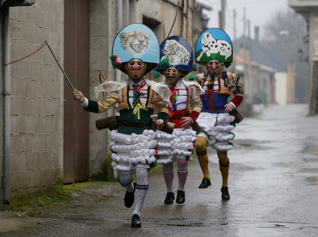 "Carnival revellers dressed as ""Peliqueiros"" run along a street in the village of Laza, Spain February 11, 2018. ""Peliqueiros"", or ancient tax collectors, pursued villagers through the streets ringing their cowbells and hitting villagers with their sticks. (Photo by Miguel Vidal/Reuters)"