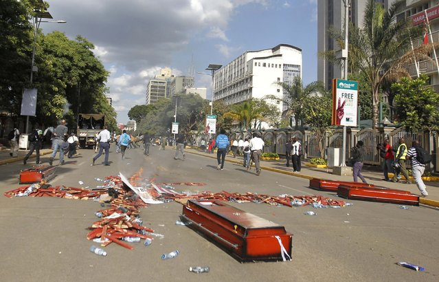 Protesters flee the scene, leaving behind coffins and wooden crosses symbolising people killed in a series of attacks, during the #OccupyHarambeeAve demonstration in Kenya's capital Nairobi November 25, 2014. (Photo by Thomas Mukoya/Reuters)