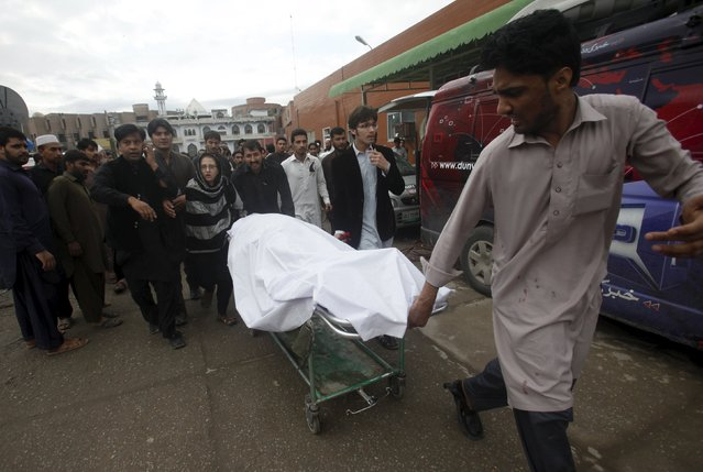 A man wheels a body of a woman, who died in an earthquake, at the Lady Reading hospital, Peshawar, Pakistan, October 26, 2015. (Photo by Fayaz Aziz/Reuters)