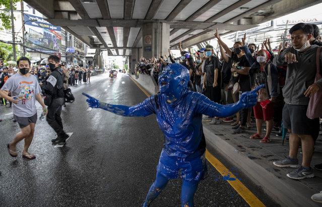 A pro-democracy protester covered in blue paint gestures on a road during a protest in Udom Suk, suburbs of Bangkok, Thailand, Saturday, October 17, 2020. (Photo by Gemunu Amarasinghe/AP Photo)
