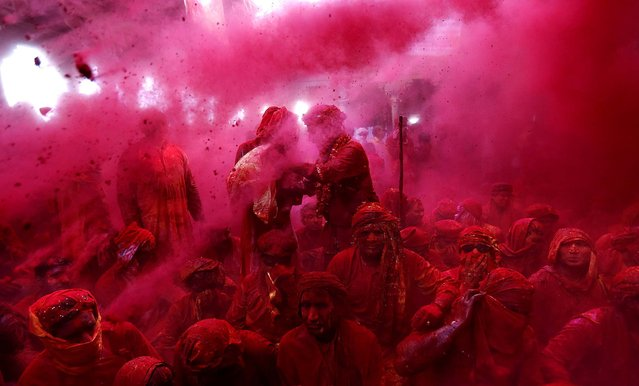 Men from the village of Nangaon are covered in colored powder as they sit on the floor during prayers at the Radha Temple. (Photo by Kevin Frayer/Associated Press)