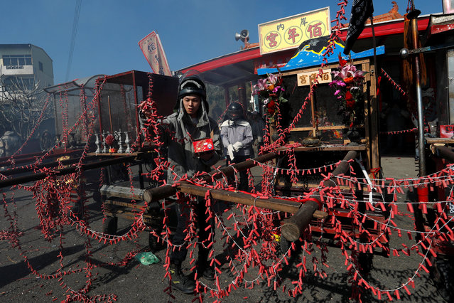 "A worshipper put firecrackers on palanquin which would be carrying statues of Guan Gong, the Chinese God of War, during ""Beehive Firecrackers"" festival at the Yanshui district in Tainan, Taiwan on March 1, 2018. (Photo by Tyrone Siu/Reuters)"