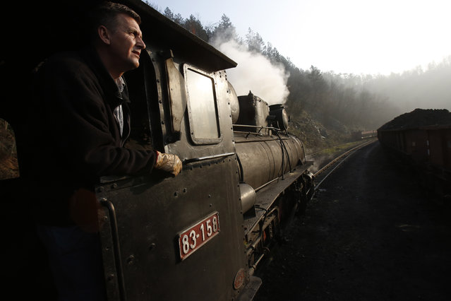 Bosnian worker Sefik Salihovic drives a steam engine in the Bosnian town of Banovici, 140 kms (86.9 miles) north of Sarajevo, on Monday, November 24, 2014. Every day, steam engines over 60 years old, defy their age and still pull wagons of coal from Banovici's coal mine to clients in nearby towns. But in the summer some of them turn into the only tourist attraction this impoverished north Bosnian town has to offer. (Photo by Amel Emric/AP Photo)