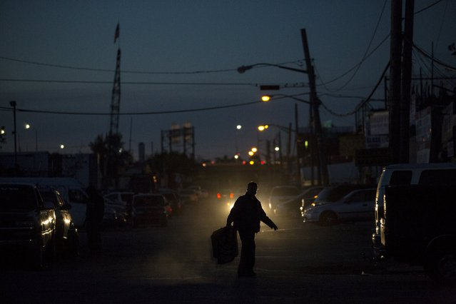 A man carries a tray through the street at dusk in the Willets Point area of Queens in New York October 26, 2015. (Photo by Andrew Kelly/Reuters)