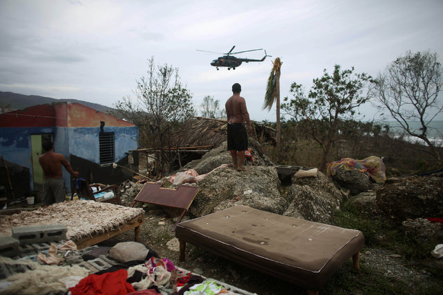 A man watches an army helicopter flying over his damaged home in Cajobabo after the passage of Hurricane Matthew, Cuba, October 6, 2016. (Photo by Alexandre Meneghini/Reuters)