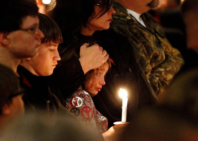 People comfort one another during a candle light vigil at St. Mary, Church of the Assumption for victims, families, friends and first responders involved with the recent fertilizer plant explosion, Thursday April 18, 2013 in  West, Texas. (Photo by Ron Jenkins/AP Photo/The Fort Worth Star-Telegram)