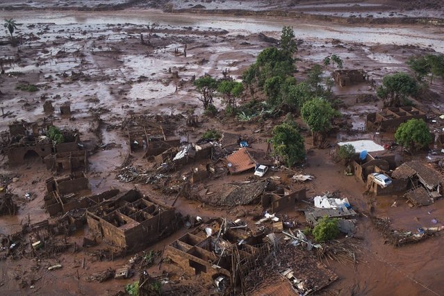 Aerial view of the debris after a dam burst on Thursday, at the small town of Bento Rodrigues in Minas Gerais state, Brazil, Friday, November 6, 2015. (Photo by Felipe Dana/AP Photo)