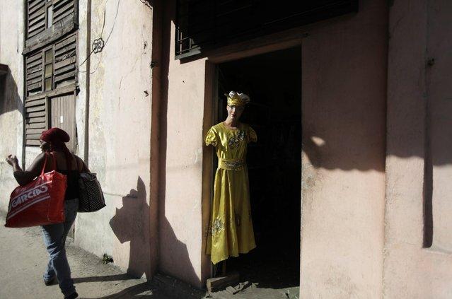A woman walks past a mannequin modelling an Afro-Cuban Santeria outfit in Havana December 17, 2014. (Photo by Enrique De La Osa/Reuters)