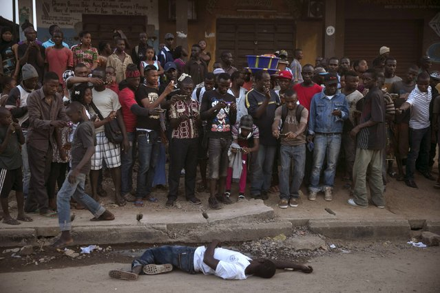 Bystanders stand around the body of a suspected Ebola victim lying in a street in the town of Koidu, Kono district in Eastern Sierra Leone, December 18, 2014. (Photo by Baz Ratner/Reuters)