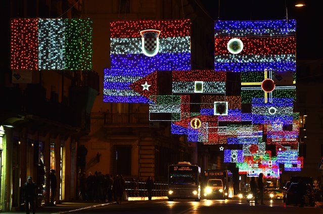 A picture shows christmas lights representing the national flags of different countries in the Via del Corso in Rome on December 9, 2014. (Photo by Gabriel Bouys/AFP Photo)