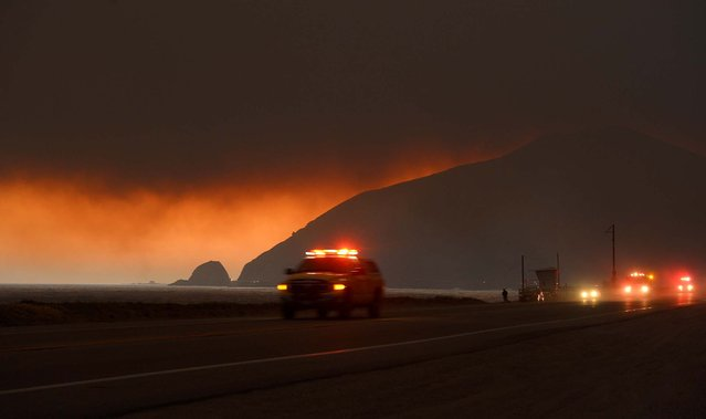 Fire department personnel drive along Pacific Coast Highway near Point Mugu as a thick layer of smoke sits overhead during a wildfire that burned several thousand acres on Thursday, in Ventura County. (Photo by Mark J. Terrill/Associated Press)