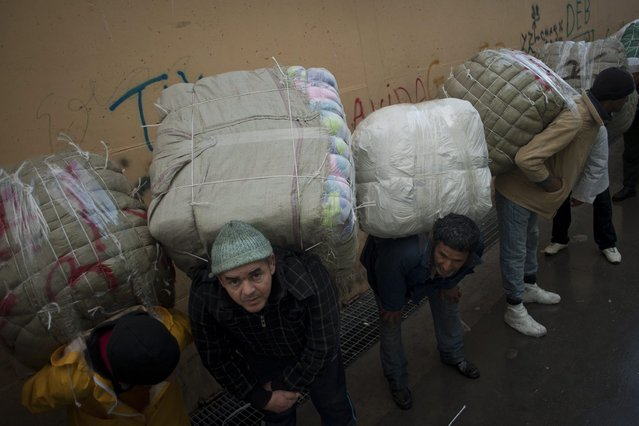 Men porters carry bundles on their backs for transport across the El Tarajal boarder separating Morocco and Spain's North African enclave of Ceuta, in Ceuta on December 4, 2014. (Photo by Jorge Guerrero/AFP Photo)