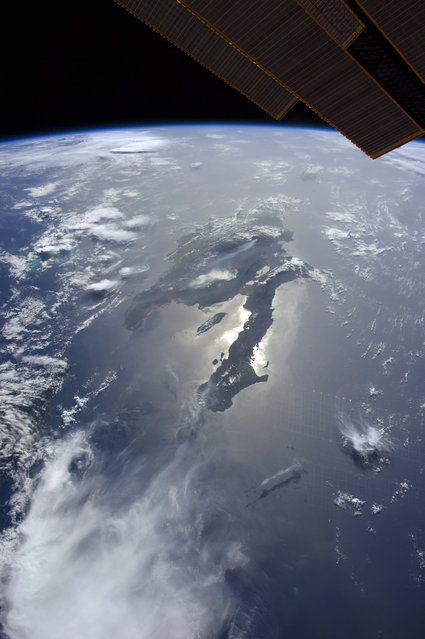 Hispaniola, ISS image. Photograph taken on 26th July 2014 by astronauts aboard the International Space Station. Hispaniola (C) lies in the Caribbean. The island is shared by two nations, Dominican Republic and Haiti. This image shows wildfire smoke plumes rising from the island. At far left are several thunderstorms on July 26, 2014 at Caribbean. (Photo by NASA/SPL/Barcroft Media)