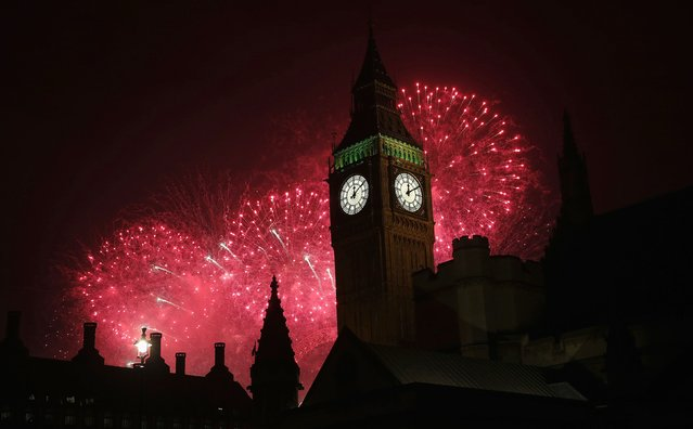 Fireworks explode behind the Houses of Parliament and Big Ben on the River Thames during New Year's celebrations in London January 1, 2015. (Photo by Suzanne Plunkett/Reuters)