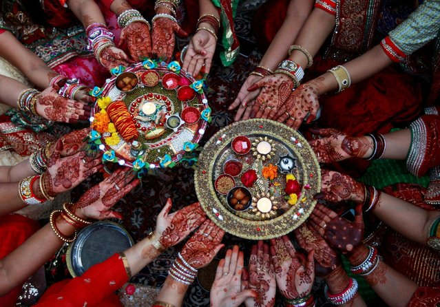 Married women pose for pictures as they perform rituals for the well being of their husbands during the Hindu festival of Karva Chauth in Ahmedabad, India, October 19, 2016. (Photo by Amit Dave/Reuters)