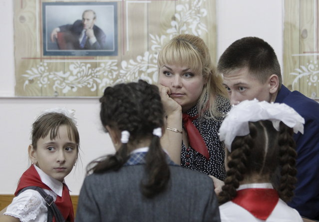 People attend a ceremony for the inauguration of new members of the Pioneer Organization, with a portrait of Russian President Vladimir Putin seen in the background, at a local school in the southern settlement of Kazminskoye in Stavropol region, Russia, November 19, 2015. (Photo by Eduard Korniyenko/Reuters)