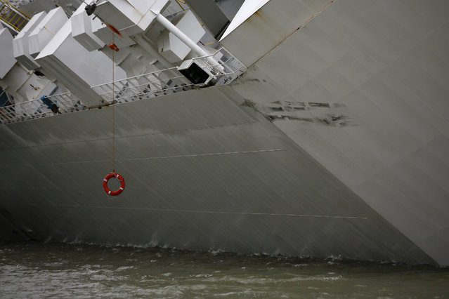 A lifebuoy hangs from the side of the Hoegh Osaka ro-ro cargo ship, operated by Hoegh Autoliners AS, as it sits grounded on Bramble Bank in the Solent near Cowes, on the Isle of Wight, U.K., on Monday, January 5, 2015. (Photo by Simon Dawson/Bloomberg)