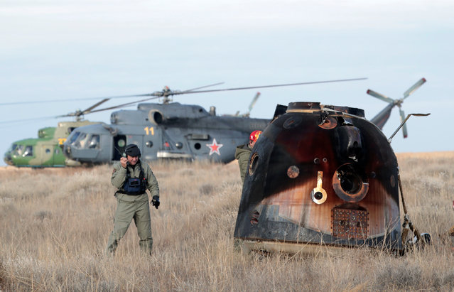 A Russian Soyuz MS space capsule stands on the ground shortly after its landing with International Space Station (ISS) crew members Kate Rubins of the U.S., Anatoly Ivanishin of Russia and Takuya Onishi of Japan, as a rescue helicopter lands nearby, outside the town of Dzhezkazgan (Zhezkazgan), Kazakhstan, October 30, 2016. (Photo by Dmitri Lovetsky/Reuters)