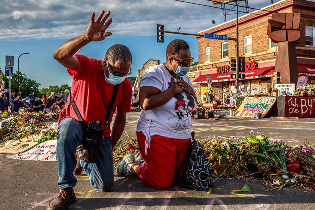 A couple kneels and raises their hands at a memorial for George Floyd following a day of demonstrations on June 13, 2020 in Minneapolis, Minnesota. Demonstrations are being held across the US following the death of George Floyd on May 25, 2020 in police custody. (Photo by Kerem Yucel/AFP Photo)